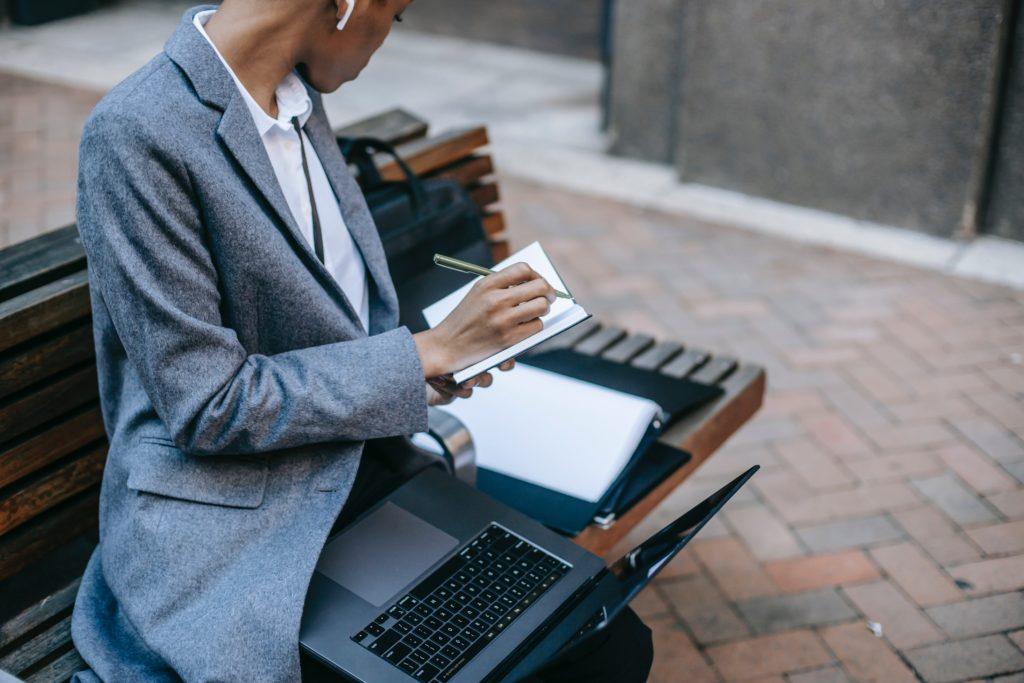 En kvinna sitter på en bänk och arbetar fokuserat med dator och anteckningsblock i knät