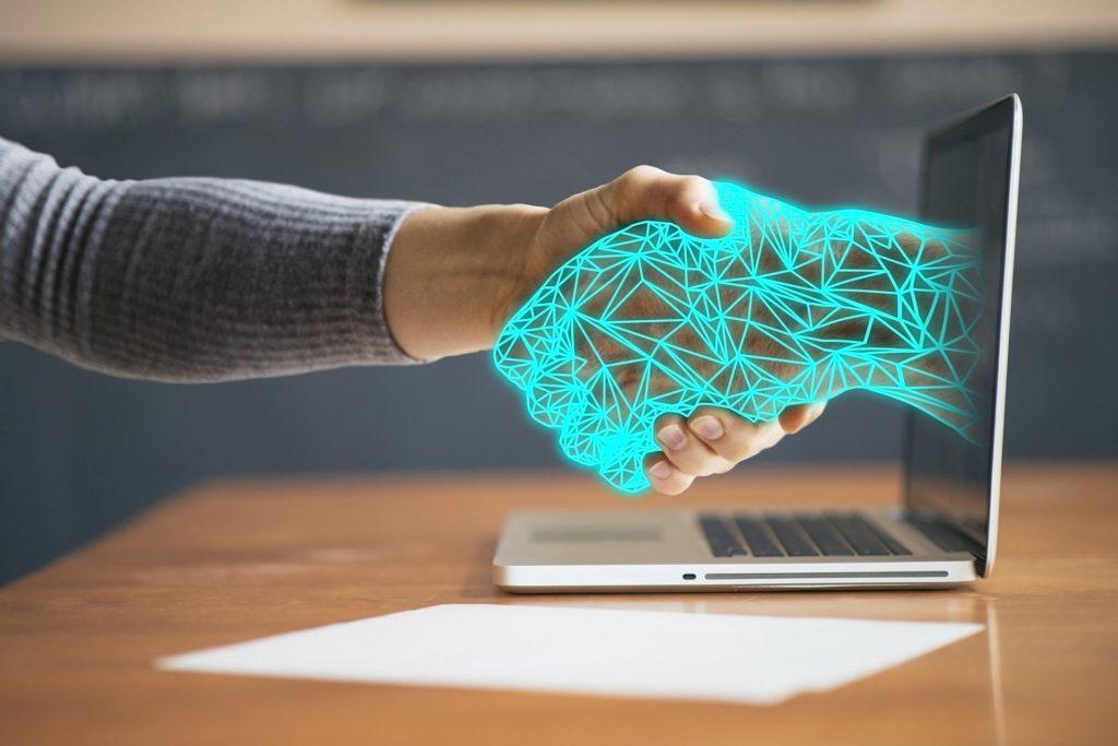 En mänsklig hand skakar en digital han. Symboliserar UCS arbeta med mjukvara och licenser
